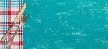 Dela sig och baktala på servett på turkosträ Royaltyfria Foton
