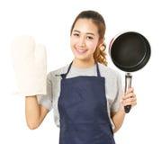 Delantal de la mujer asiática y pote el mostrar que llevan con Oven Glove Imagen de archivo