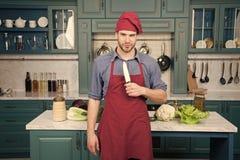 Delantal del desgaste del cocinero del hombre que cocina en cocina Cuchillo de cer?mica agudo del uso del hombre Herramienta del  imagenes de archivo