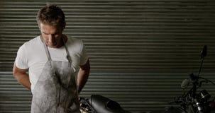 Delantal que lleva del mecánico de sexo masculino en el garaje 4k de la reparación de la moto almacen de metraje de vídeo