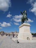 Delante de la estatua de Versalles y de rey Louie XIV Fotografía de archivo
