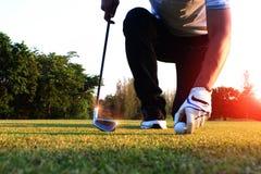 Delante de los golfistas, coja la pelota de golf en el campo foto de archivo