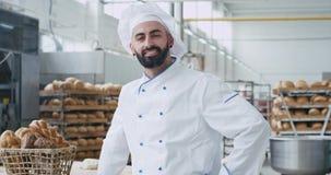Delante del retrato de la cámara de un panadero comercial de la cara del hombre apuesto en un rato grande sonriente del uniforme  metrajes