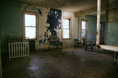 Delapidated与空的生锈的床的医院大厦 免版税库存照片