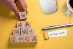 Delar av digitalt lära som symboler av kuber och ordet 'som e-lär ', arkivfoto