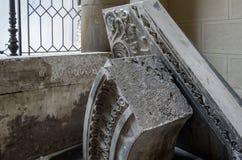 Delar av forntida stenar sned kolonner på bakgrunden av en forntida vägg med ett fönster arkivbild
