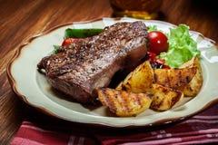 Delar av grillad nötköttbiff med grillad potatisar och paprika Royaltyfria Foton