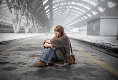 Delay. Young woman waiting on the platform of a train station Stock Photos