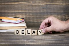 Delay. Wooden letters on the office desk. Informative and communication background stock photos