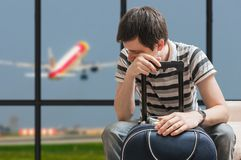 Delayed aeroplane concept. Tired passenger is sitting with baggage in airport. Royalty Free Stock Photo