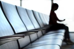 Delayed and cancelled flight concept. Silhouette woman looking her watch in airport terminal to see the time in airport waiting room and departure lounge Stock Photos