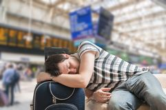 Delayed train concept. Tired and exhausted passenger is sleeping. Stock Photo