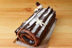 Delectable Buche de Noel or Chocolate Yule Log Cake for Christmas Sprinkle with Icing Sugar. On the Wooden Table stock photography