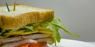 Delectable deli sandwich with toothpicks on top. Close up shot of a delectable deli sandwich with lettuce, cheese, meat, and tomatoes. Green and yellow royalty free stock image