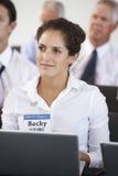 Delegado fêmea que escuta a apresentação na conferência que faz anotações no portátil imagens de stock