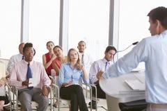 Delegados do negócio que escutam a apresentação na conferência foto de stock