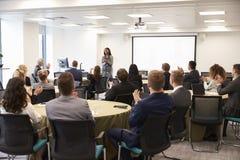 Delegater som applåderar affärskvinnan Making Presentation royaltyfri bild
