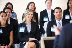 Delegates Listening To Speaker At Conference. Smiling Royalty Free Stock Photos