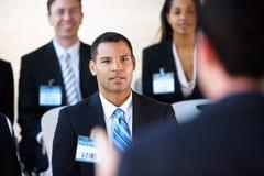 Delegati che ascoltano l'altoparlante Fotografia Stock