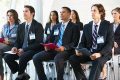 Delegati che ascoltano l'altoparlante alla conferenza Immagine Stock
