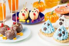 Deleites doces de Dia das Bruxas, conceito do alimento do partido Os queques brancos e azuis com caras fecham-se acima imagem de stock
