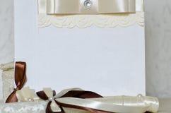 Delen av bröllopkortet med bandet och snör åt Vit bakgrund, utrymme för text Arkivfoton