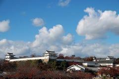 Delen av byggnad på den Himeji slotten som ut ser från sida med det röda höstträdet och bakgrund för blå himmel Arkivfoto