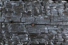 Delen av den brände till kol timret och rostigt spikar bakgrund arkivbild