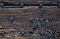 Delen av den forntida trädörren med bultat enormt spikar royaltyfri foto