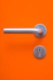 Delen av den orange dörren med metallhandtaget Fotografering för Bildbyråer