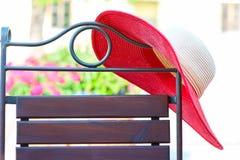 Delen av elegant metall buktade stol och den röda sommarhatten på uteplats Fotografering för Bildbyråer