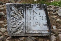 Delen av en latinsk inskrift på Ulpia Traiana Sarmizegetusa fördärvar Royaltyfri Bild