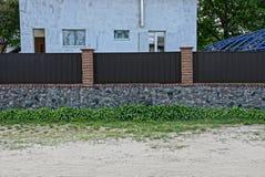 Delen av en privat grå färg-grå färg fäktar gjort av järn och stenar på gatan Arkivbild