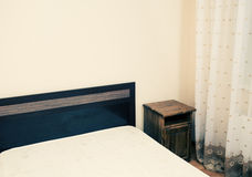 Delen av ett rum med säng i ett hörn colorized sikt Royaltyfria Foton