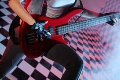 Delen av förkroppsligar av kvinnan som leker den elektriska gitarren royaltyfri foto