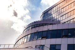Delen av fasaden av en byggnad avslutade sig med moderna material och molnen och solen det reflektera i fönstren som en bac Arkivfoto