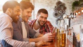 Delend Nieuws met Smartphone en Drinkend Bier in Bar stock afbeeldingen