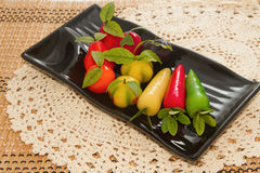 Deletable imitation fruits in black plate Stock Images
