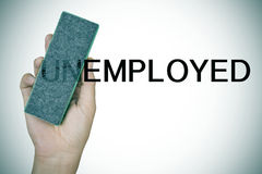Deleting the prefix UN in the word unemployed with an eraser Stock Photos
