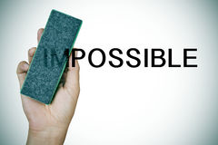 Deleting the word impossible with an eraser. Closeup of the hand of a young man deleting the word impossible with an eraser Stock Photo
