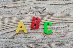 Deletreo de ABC de letras plásticas coloridas en fondo de madera Foto de archivo