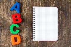 Deletreo de ABCD y cuaderno en blanco Fotografía de archivo