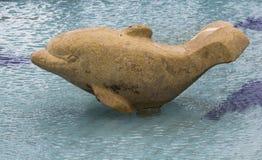 Delfino di pietra nell'acqua Fotografie Stock