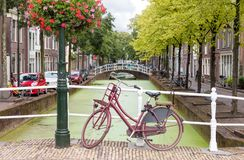 Delft city view in the Netherlands with water canal and vintage bicycle. On the bridge in summer royalty free stock photos
