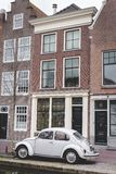 Delft, die Niederlande - 6. Januar 2019: Volkswagen Beetle parkte vor niederländischem Kanalhaus in Delft lizenzfreies stockfoto