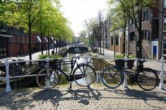 Delft, Nederland - 21 April, 2019: Twee fietsen voor een historisch kanaal in het centrum van Delft stock foto