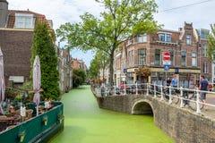 DELFT, NEDERLAND - 27 AUGUSTUS, 2017: Toeristen en klanten op de smalle straten langs de kanalen van Delft op een de zomerdag in  royalty-vrije stock afbeelding