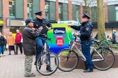 DELFT, PAYS-BAS - 18 janvier 2014 : Deux policiers néerlandais amicaux sur une bicyclette dans une place occupée à Delft, Pays-Ba image stock