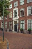 Street with facade and entrance gate of elegant brick building on cloudy day in Delft. stock image