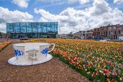 DELFTFAJANS Nederländerna - APRIL 26, 2018: En tulpanträdgård framme av den nya townhallen/järnvägsstationen i delftfajans fotografering för bildbyråer